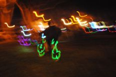 Cyclists with lights around the bike wheels speed through a San Jose park as a Bike Party, a monthly ride, takes off.